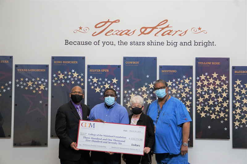 COM Foundation receiving a check from the Dickinson Management District No. 1